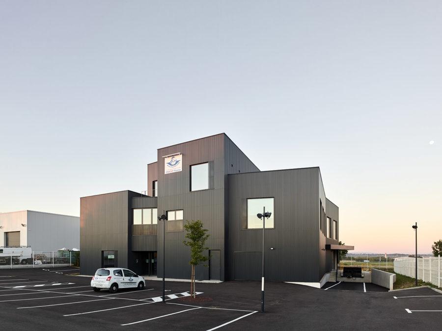 bâtiment architecte bureaux entrepôts façade bardage métallique ondulé anthracite Lyon aéroport